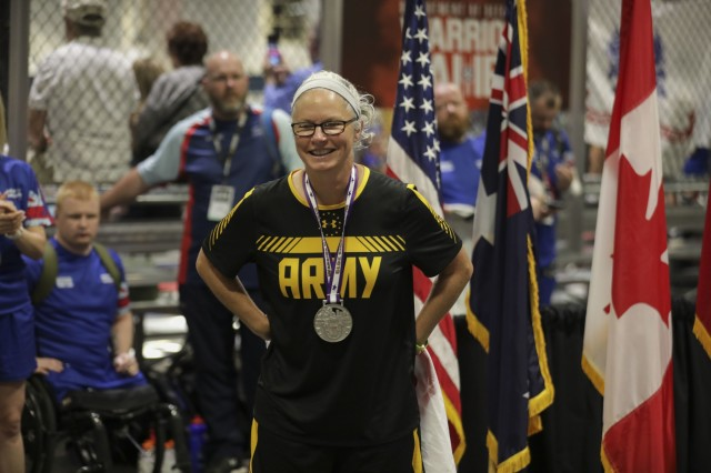 U.S. Army Master Sgt. Cinnamon Wright recevices a silver medal for indoor rowing June 25, 2019 at the Tampa Convention Center. The DoD Warrior Games are conducted June 21-30, hosted by Special Operations Command, Tampa, Florida. It is an adaptive sports competition for wounded, ill and injured service member and veterans. Approximately 300 athletes representing teams from teams from the U.S. Army, Marine Corps, Navy, Air Force, Special Operations Command, United Kingdom Armed Forces, Australian Defence Force, Canadian Armed Forces, Armed forces of the Netherlands, and the Danish Armed Forces will compete in archery, cycling, shooting, sitting volleyball, swimming, track, field, wheelchair basketball, indoor rowing, powerlifting, and for the first time in Warrior Games history, golf, wheelchair tennis, and wheelchair rugby. (U.S. Army Video by Spc. Evens Milcette Jr.)