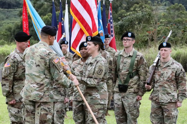(Right to left) Command Sgt. Maj. Tammy M. Everette, outgoing command sergeant major, 500th Military Intelligence Brigade-Theater (MIB-T) passes the Brigade colors to Col. David P. Elsen, commander, 500th MIB-T, during a Flying V ceremony on Schofield Barracks, Hawaii, June 26. Everette relinquishes responsibility as the Brigade command sergeant major to Command Sgt. Maj. John R. Parker.