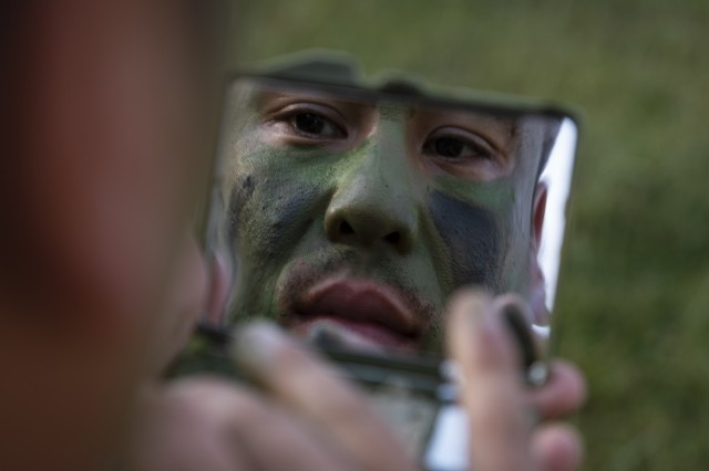U.S. Army Staff Sgt. True Thao, a Public Affairs Mass Communication Specialist with the 358th Public Affairs Detachment, applies face camouflage in preparation for the Wet Gap Crossing, the culminating event for Saber Guardian, June 21, 2019. Exercises such as Saber Guardian 19, continue to increase participating nations' readiness and capacity to conduct full spectrum military operations. They send a clear message that the U.S. and its allies and partners work skillfully together. (U.S. Army photo by Sgt. Thomas Mort)