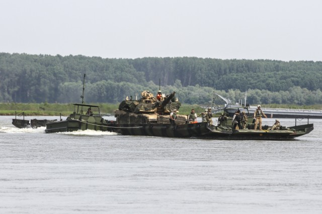 An M1 Abrams tank assigned to 1st Battalion, 16th Infantry Regiment, 1st Armored Brigade Combat Team, 1st Infantry Division, crosses the Danube river on a raft during Saber Guardian 19 at Bordusani, Romania, June 20, 2019. Saber Guardian 2019 is an exercise co-led by Romanian Land Forces and U.S. Army Europe designed to improve the integration of multinational combat forces. (U.S. Army photo by Staff Sgt. True Thao)