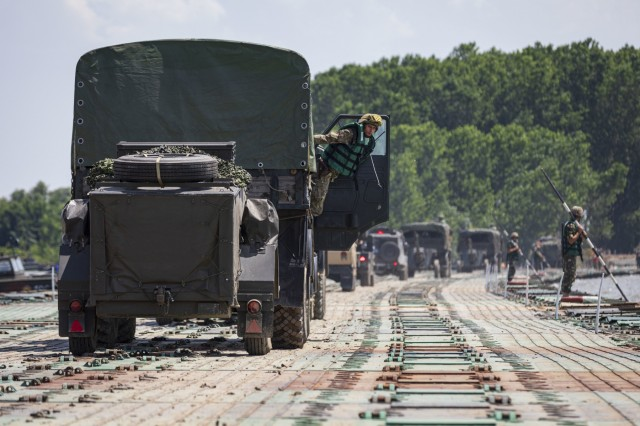 Military vehicles cross a floating bridge during the multinational operation, the Wet Gap Crossing (WGX), June 22, 2019. The WGX is the culminating event of Saber Guardian 2019, which continue to increase participating nations' readiness and capacity to conduct full spectrum military operations. They send a clear message that the U.S. and its allies and partners work skillfully together. (U.S. Army photo by Sgt. Thomas Mort)