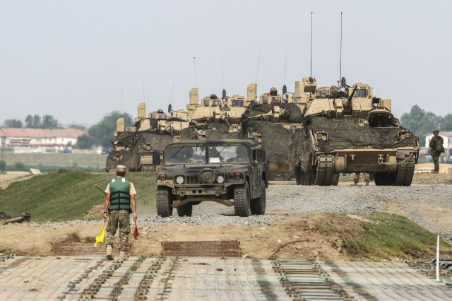U.S. Army vehicles await to cross the Danube river during Saber Guardian at Bordusani, Romania, June 20, 2019. Saber Guardian 2019is an exercise co-led by Romanian Land Forces and U.S. Army Europe designed to improve the integration of multinational combat forces. (U.S. Army photo by Staff Sgt. True Thao)