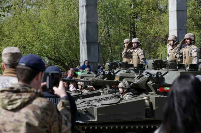 Latvian Soldiers ride in a military vehicle rendering a salute to the distinguished guests attending the traditional regional military parade of May 4 in Jekabpils, Latvia, on May 4, 2019. Numerous countries had representatives attend the parade in celebration of the Latvian War for Independence and their Armed Forces. (U.S. Army photo by Sgt. Kyle Larsen)