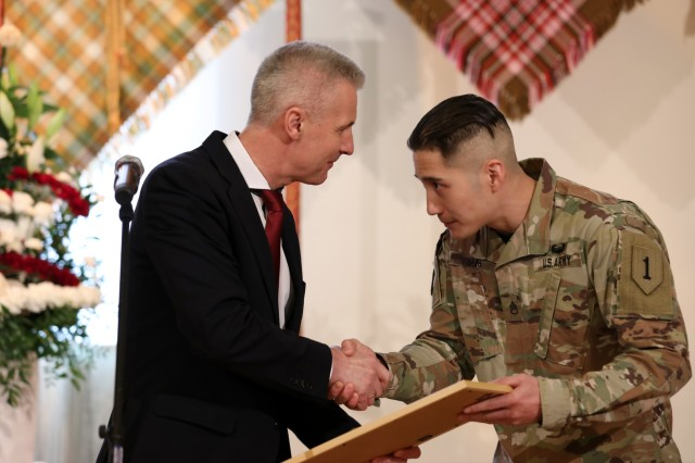 Latvia's Deputy Prime Minister and Minister of Defense, Dr. Artis Pabriks, left, awards an U.S. Soldier, Staff Sgt. Stephen Yang, during the Latvian traditional regional military parade of May 4 in Jekabpils, Latvia, on May 4, 2019. Yang and his colleague, Army Capt. Logan Gorges, both assigned to Task Force Nightmare North, 3-1 Assault Helicopter Battalion, 1st Combat Aviation Brigade, 1st Infantry Division, used their medical training to apply lifesaving measures when an elderly Latvian man had a seizure. (U.S. Army photo by Sgt. Kyle Larsen)