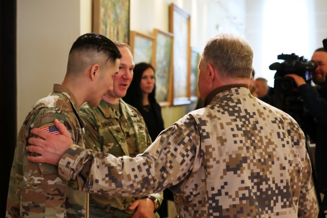 Latvia's Deputy Prime Several high ranking officials from various nations congratulate two U.S. Soldiers, Army Capt. Logan Gorges, center, and Staff Sgt. Stephen Yang, left, following an award ceremony that proceeded the Latvian traditional regional military parade of May 4 in Jekabpils, Latvia, on May 4, 2019. Gorges and Yang, both assigned to Task Force Nightmare North, 3-1 Assault Helicopter Battalion, 1st Combat Aviation Brigade, 1st Infantry Division, used their medical training to apply lifesaving measures when an elderly Latvian man had a seizure. (U.S. Army photo by Sgt. Kyle Larsen)