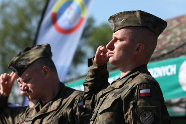 A Polish soldier salutes the country's flag as another soldier hoists it up the flag pole at the beginning of the Tobruq Legacy 19 closing ceremony June 19, 2019, in Ustka, Poland. TOLY19 is an annual multinational air defense exercise which included more than 3,000 personnel from 13 nations, which Poland hosted and directed throughout their country. (U.S. Army photo by Sgt. Kyle Larsen)