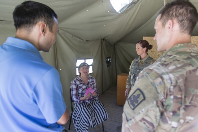 Capt. Brandon Teskey (far right), commander of D Company, 1st Battalion, 158th Infantry Regiment, Arizona Army National Guard, and Staff Sgt. Jenna Ross, a squad leader in D Company, 1st Battalion, 158th Infantry Regiment, Arizona Army National Guard, meet with a civilian role player during training at Chilikemer Training Area near Almaty, Kazakhstan, June 25, 2019, as part of Exercise Steppe Eagle 19. The exercise is an annual U.S. Army Central-led exercise that promotes regional stability and interoperability in the Central and South Asia region. (Photo by U.S. Army Maj. Kevin Sandell)