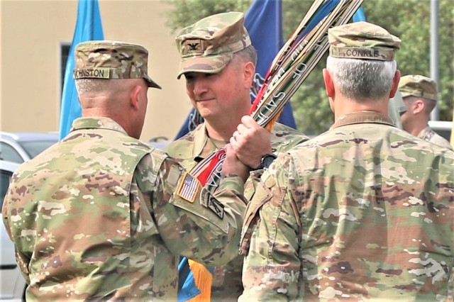 Col. Bryan M. Love, commander, 207th Military Intelligence Brigade -- Theater (MIB-T), receives the guidon from Maj. Gen. Gary W. Johnston, commanding general, U.S. Army Intelligence and Security Command (INSCOM), during the 207 MIB-T change of command ceremony June 11.