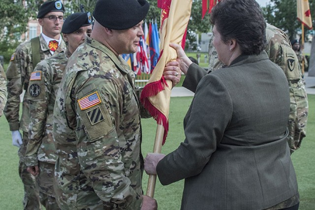 Brenda Lee McCullough, director for Installation Command - Readiness, passes the Fort Stewart-Hunter Army Airfield unit colors, June 20, as Col. Bryan Logan assumes command of the garrison. (U.S. Army photo by Catherine D. Johnson)