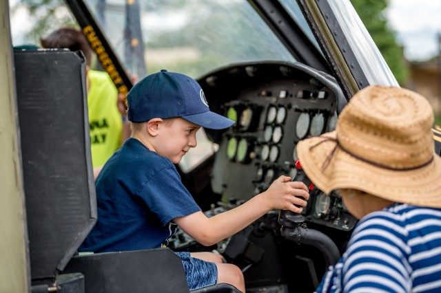 """Children of all ages formed a long line to see """"Miss Mini"""" -- a historic UH-1C gunship. Visitors were able to explore the cockpit of the helicopter, which was flown during the Vietnam War."""
