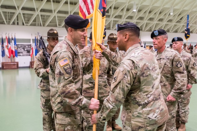 Col. Adam Hilburgh, incoming brigade commander, left, receives the brigade colors from Col. Daryl Hood, U.S. Army CBRN School commandant, during the joint ceremony June 24.