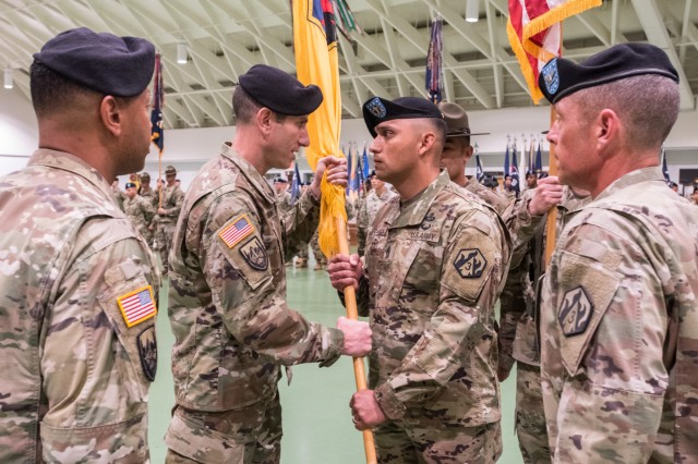 Command Sgt. Maj. Jorge Arzabala Jr., right, receives the 3rd Chemical Brigade colors from new 3rd Chem. Bde. commander, Col. Adam Hilburgh. Hilburgh and Arzabala assumed leadership of the brigade in a combined ceremony June 24.