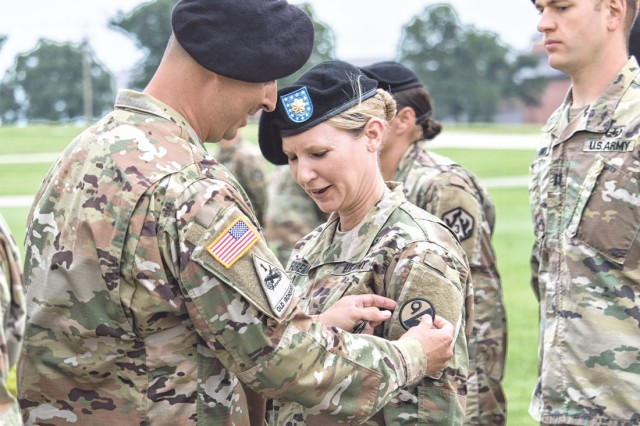 Lt. Col. Ramon Salas, 58th Transportation Battalion commander, places a 94th Training Division patch on the sleeve of Maj. Melanie Foreman during the ceremony June 18.