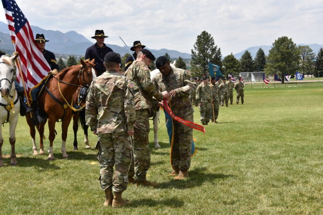 Lt. Col. Donald Brooks, outgoing 1st Space Battalion commander, and 1st Space Battalion Command Sgt. Maj. Tracey Rosser attach the U.S. Army Superior Unit Award streamer to the battalion guidon June 26 prior to Brooks' change of command ceremony at Fort Carson, Colorado. The award recognizes outstanding meritorious performance by a unit during peacetime, in which they display meritorious performance of a difficult and challenging mission carried out under extraordinary circumstances. (U.S. Army photo by Dottie White)