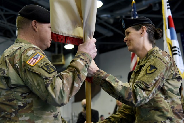 Col. Renee L. Mann, the outgoing commander of the 403rd Army Field Support Brigade, passes the colors to Maj. Gen. Duane A. Gamble, the commanding general of the U.S. Army Sustainment Command, during a change of command ceremony June 28 at Camp Walker, Republic of Korea. Mann passing Gamble the colors represents her relinquishing command.