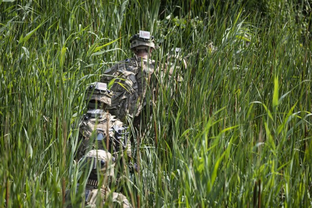 A squad of infantrymen with 1st Battalion, 16th Infantry Regiment, 1st Armored Brigade Combat Team, 1st Infantry Division, maneuver through a trench on an air assault mission, during the wet gap crossing exercise and Saber Guardian 19, June 20, 2019. Exercises such as Saber Guardian 19, continue to increase participating nations' readiness and capacity to conduct full spectrum military operations. They send a clear message that the U.S. and its allies and partners work skillfully together. (U.S. Army photo by Sgt. Thomas Mort)
