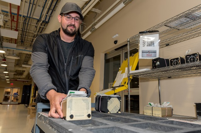 Electronics Worker Brandon Carey uses foam cutouts and a pneumatic wheeled cart to move sensitive precision measuring devices during each stage of the overhaul process.