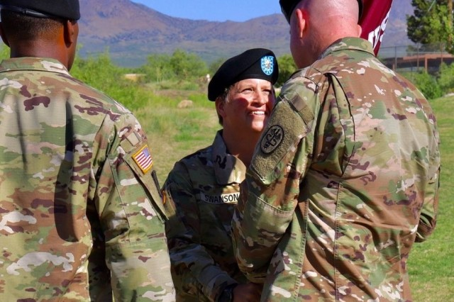 Lt. Col. Kirsten Swanson relinquishes command of the McAfee U.S. Army Health Clinic by passing the unit flag to Col. Erik Rude, Commander of William Beaumont Army Medical Center which the McAfee Clinic falls under.