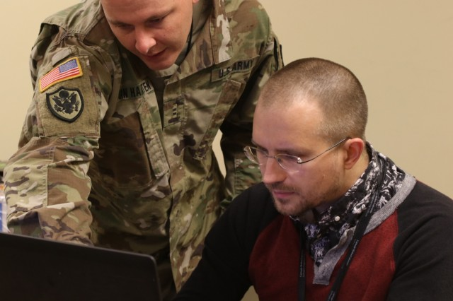 U.S. Army Chief Warrant Officer 2 Michael D. Van Haaften, currently assigned to the Army Reserve Cyber Operations Group (ARCOG), North Central Cyber Protection Center, 335th Signal Command (Theater), discusses a phase of his team's network operations strategy with a Cyber X-Games 2019 facilitator from the Carnegie Mellon University Software Engineering Institute, during the annual cyber training event sponsored by the ARCOG, June 15 at Moffett Field, California. X-Games 19 was a five-day exercise hosted by the 63rd Readiness Division. The competition exercise focused on the protection of Department of Defense assets through joint force collaboration and welcomed multinational partners to observe how the U.S. Army Reserve Cyber Force plans and trains. (U.S. Army Reserve photo by Sgt. Erick Yates)