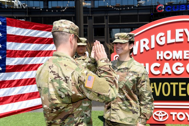 Sgt. Maribel Meraz, assigned to the 85th U.S. Army Reserve Support Command, headquartered in the northwest suburbs of Chicago, states the Oath of Enlistment at Gallagher Way, adjacent to the Chicago Cubs Wrigley Field, June 27, 2019, for a third six-years in the Army Reserve. Meraz enlisted in the Army Reserve in 2008 and has served on two deployments in support of Operation New Dawn and Operation Enduring Freedom. She shared that in a house divided between the Chicago Cubs and Chicago White Sox, she is a Cubs fan and she gets that from her mother. Meraz conducted her reenlistment with Soldiers from her command and her mother present. (U.S. Army Reserve photo by Anthony L. Taylor)