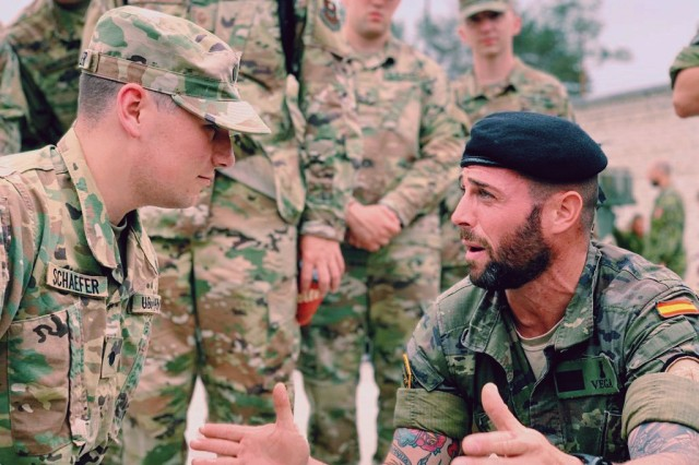 Cadet Evan Schaefer (left), from Indiana University, speaks and translates in Spanish to Spanish North Atlantic Treaty Organization (NATO) personnel on June 18 at Camp Adazi.