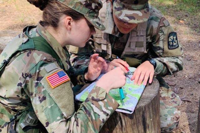 Cadet Chole Bullock (left), from the University of Vermont, and Cadet TeAta Gutierrez (right), from Azusa Pacific University, participate in the 11k land navigation course at Camp Adazi on June 10.