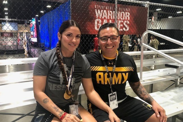 Army Captain David Espinoza and his wife Elizabeth watching what they say is the greatest reality show you could see, at the 2019 Department of Defense Warrior Games in Tampa Florida. June 27, 2019. The DoD Warrior Games an adaptive sports competition for wounded, ill, and injured service members and veterans. Approximately 300 athletes, representing teams from the Army, Marine Corps, Navy, Air Force, Special Operations Command, United Kingdom Armed Forces, Australian Defense Force, Canadian Armed Forces, Armed Forces of the Netherlands, and the Danish Armed Forces will compete in archery, cycling, shooting, sitting volleyball, swimming, track, field, wheelchair basketball, indoor rowing, powerlifting, and for the first time in Warrior Games history, golf, wheelchair tennis, and wheelchair rugby. (Photo by MaryTherese Griffin)
