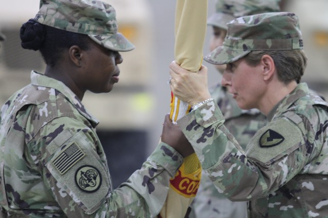 Colonel Mary O.B. Drayton, left, incoming commander, 408th Contracting Support Brigade, accepts the unit colors from Col. Christine A. Beeler, deputy to the commanding general for outside the continental United States for Army Contracting Command, during the change of command ceremony June 27, 2019, at Camp Arifjan, Kuwait. This is Drayton's third assignment within the 408th CSB.
