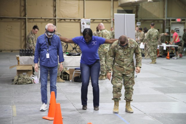 Army Master Sgt. Vernitta Thomas, center, safety noncommission officer in charge, U.S. Army Central, assists two ARCENT Safety Fair attendees as they try to complete a field sobriety test while wearing specially designed goggles that simulate the effects of drugs and alcohol, June 21, 2019, at Camp Arifjan, Kuwait. The safety fair is a highlight of the U.S. Army Central's 101 Critical Days of Summer safety program that encourages leaders to engage with their Soldiers and to stress the importance of being safe in everything they do.