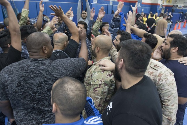 Kuwaiti armed forces participate in a team huddle before a combatives tournament at Camp Arifjan, Kuwait, June 23, 2019. U.S. Army Central hosts events such as the combatives tournament to strengthen its relationship and build partner capacity with the Kuwaitis. USARCENT operates throughout the Middle East region and appreciates the generosity of the host nation's willingness to maintain bilateral defense relationships. (Army Reserve photo by Sgt. Christopher Lindborg)