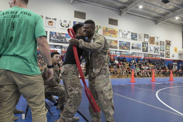 United States Army Staff Sgt. Kenry Trowers, right, a noncommissioned officer in charge, Combined Joint Task Force -Operation Inherent Resolve, celebrates after winning a fight during a combatives tournament at Camp Arifjan, Kuwait, June 23, 2019. U.S. Army Central hosts events such as the combatives tournament to strengthen its relationship and build partner capacity with the Kuwaitis. USARCENT operates throughout the Middle East region and appreciates the generosity of the host nation's willingness to maintain bilateral defense relationships. (Army Reserve photo by Sgt. Christopher Lindborg)