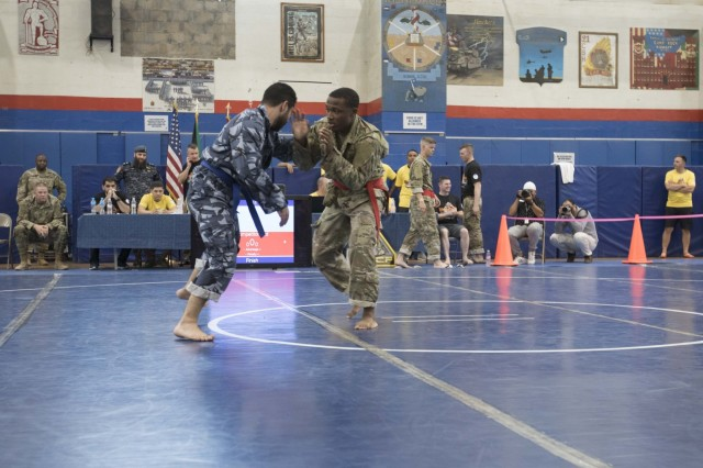 United States Army Spc. Luciano Thomas, right, a signal support systems specialist assigned to 18th Field Artillery Brigade, Headquarters and Headquarters Battery, competes in a combatives tournament at Camp Arifjan, Kuwait, June 23, 2019. U.S. Army Central hosts events such as the combatives tournament to strengthen its relationship and build partner capacity with the Kuwaitis. USARCENT operates throughout the Middle East region and appreciates the generosity of the host nation's willingness to maintain bilateral defense relationships. (Army Reserve photo by Sgt. Christopher Lindborg)