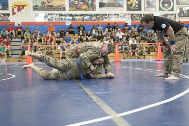 United States Army Sgt. Linsey Williams, bottom, a public affairs mass communications specialist assigned to the 34th Red Bull Infantry Division, Minnesota Army National Guard, maneuvers out of a hold by Capt. Joshua Harmon, a chaplain with 8th Battalion, 229th Aviation Regiment, during a combatives tournament at Camp Arifjan, Kuwait, June 23, 2019.  U.S. Army Central promotes good unit moral which enhances unit cohesion and reinforces the importance of excellence. (Army Reserve photo by Sgt. Christopher Lindborg)