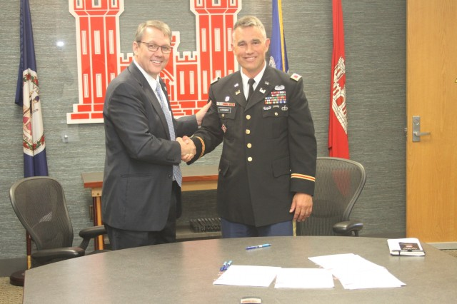 Norfolk City Manager Doug Smith and Col. Patrick Kinsman, commander of Norfolk District, U.S. Army Corps of Engineers, shake hands after signing the Norfolk Coastal Storm Risk Management design agreement June 28 at the Waterfield Building on Fort Norfolk, Virginia. USACE and city officials will now proceed with the Preconstruction Engineering and Design Phase. The project, which could lead to $122 million in annual net benefits for the city, is aimed at reducing damage from coastal storms to local businesses, residents and infrastructure. (U.S. Army photo/Vince Little)