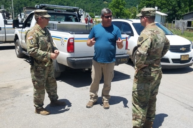 U.S. Army Capt. Steven Frey and Chief Warrant Office 2 David Marple talk with a representative of the West Virginia Division of Highways July 1, 2019, in Randolph County, West Virginia. Frey and Marple are a liaison officer team from the West Virginia National Guard who are assisting the Randolph County Emergency Operations Center with coordinating response and recovery from a flooding event on June 30, 2019.