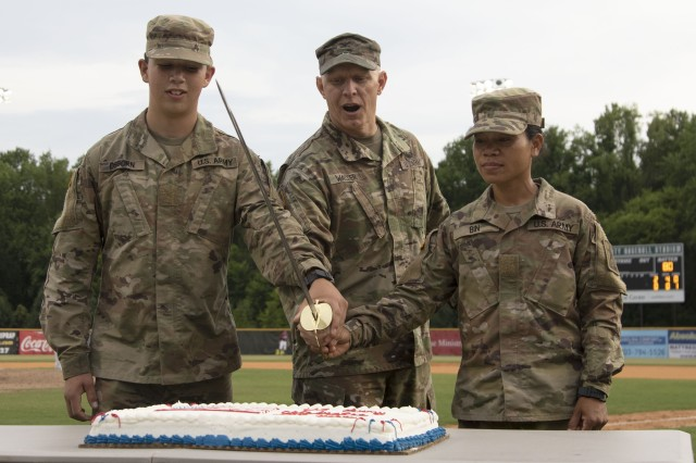 Pvt. Brent Osborn (left) and Spc. Thary Bin (right) of 2nd Battalion, 60th Infantry Regiment cut a birthday cake with Col. Douglas Walter (center), Army Training Center and Fort Jackson deputy commanding officer, during a military appreciation baseball game June 22. The Lexington Blowfish invited the Soldiers to attend the game to show their appreciation for their service to the nation.