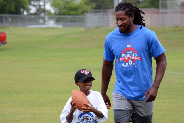 Andre Roberts, wide receiver for the Buffalo Bills, provides realistic rushing pressure for participants during quarterback drills at the Fort Jackson Family and MWR Youth Sports Football ProCamp held on the installation Jun18-19. Roberts hosted this year's ProCamp to provide the community youth an opportunity to learn from and experience various coaching fundamental football skills.