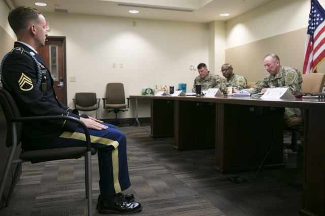 Staff Sgt. Matthew Whitney, assigned to the 3rd Infantry Division, sits at the position of attention while being questioned by sergeants major during a board as part of the 2019 XVIII Airborne Corps Noncommissioned Officer and Soldier of the Year competition June 28, 2019 on Fort Bragg, N.C. The Army board is a mental test to identify which Soldier is equipped with the most knowledge on Army related material. (U.S. Army photo by Pfc. Nathaniel Gayle, 22nd Mobile Public Affairs Detachment)