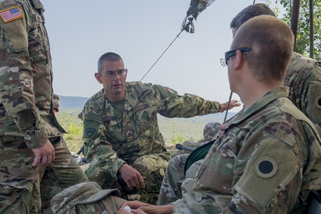 Hungarian Defence Forces Command Sgt. Maj. Arpad Virincsik (center), command sergeant major of the 101st Field Artillery Battalion, briefs Ohio National Guard Soldiers with Battery A, 1st Battalion, 134th Field Artillery Regiment in preparation for live-fire artillery training June 12, 2019, near Varpalota, Hungary. The 101st helped host BREAKTHROUGH 19, a Hungarian national training exercise that utilized multiple artillery systems from the Hungarian Defence Forces, U.S. Army Europe and Army National Guard units to create a collective capability that increases the interoperability and readiness of the participating militaries.