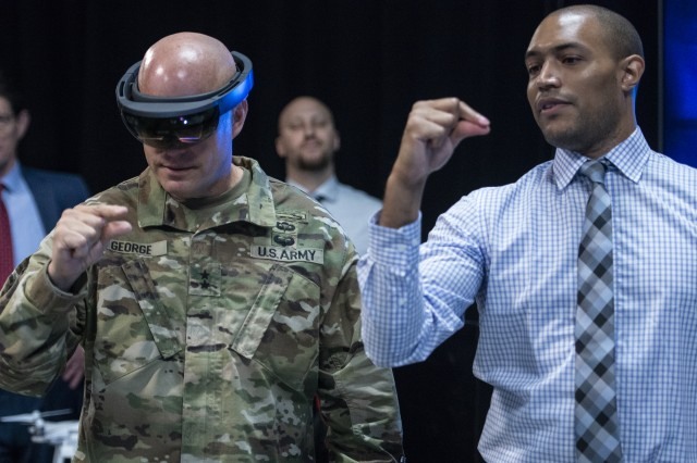 Austin Drexler, researcher at the Institute for Creative Technology in Los Angeles, helps Maj. Gen. John George use special interactive goggles to view One World Terrain 3D interactive simulation data. George is deputy director, Army Futures and Concepts Center.