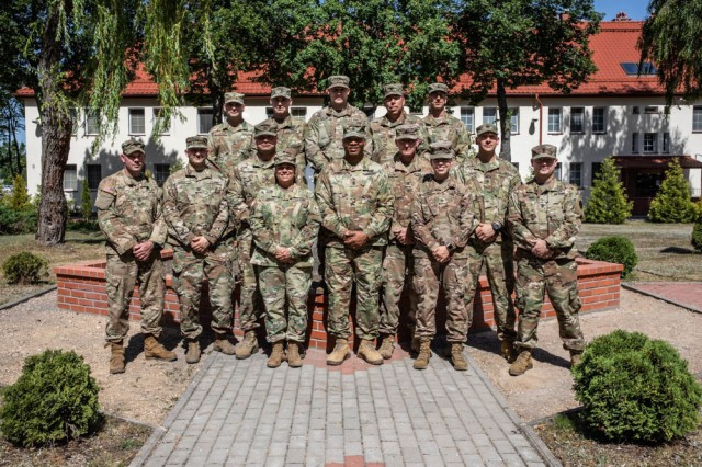 The Command Sgt. Maj of the Army National Guard, Command Sgt. Maj. John F. Sampa (first row, center) and Chief Warrant Officer 5, Teresa A. Domeier (left of Sampa) pose with Battle Group Poland leadership during their visit to Bemowo Piskie Training Area, Poland, June 30.