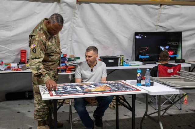 Army National Guard Command Sgt. Maj. John F. Sampa and Sgt. Robert Davidson of the 278th Armored Cavalry Regiment talks about puzzles during his visit to the Bemowo Piskie Training Area, Poland, June 30.