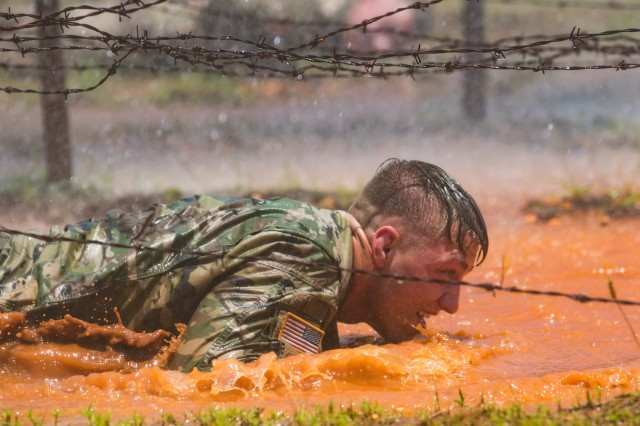 A U.S. Army Soldier low crawls under barbed wire during an obstacle course June 24, 2019 on Fort Bragg, N.C. The obstacle course is part of the 2019 XVIII Airborne Corps Noncommissioned Officer and Soldier of the Year competition.