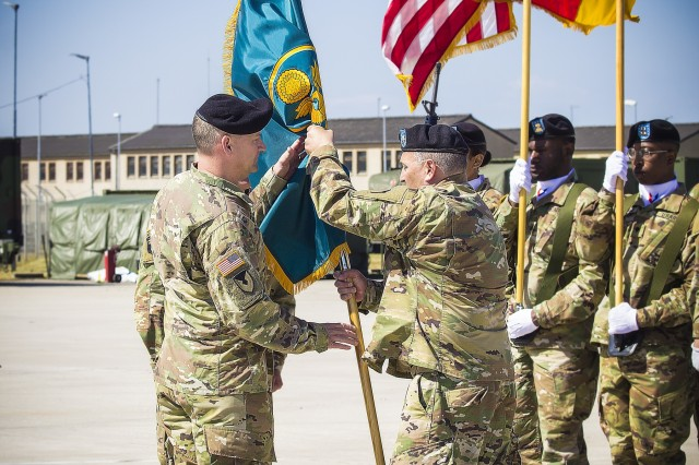 Lt.  Col. Scott Boyington, outgoing commander, Army Field Support Battalion - Mannheim, passes the battalion colors to Col. Grant L. Morris, 405th AFSB commander, at a change of command ceremony,  at Coleman Worksite in Mannheim, Germany, July 2.