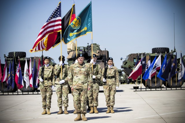 Lt. Col. Jason Knapp, incoming commander, Army Field Support Battalion- Mannheim, signs on as commander, in front of the battalion's color guard, during a change of command ceremony on Coleman Worksite in Mannheim, Germany, July 2.