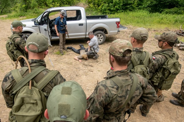 Members of the Polish Territorial Defense Forces receive training in checkpoint vehicle clearing techniques from members of West Virginia Army National Guard (WVARNG) Special Forces during Ridge Runner 19-02, June 24, 2019, in West Virginia. Ridge Runner is a WVARNG training program that provides various National Guard, active duty, and North Atlantic Treaty Organization (NATO) ally nation armed forces with training in irregular and asymmetrical warfare tactics and operations. (This photo has been altered for security purposes by blurring out faces.)
