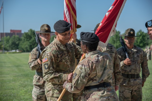 Incoming USAES Commandant Col. Mark Quander (left) takes the colors from Maj. Gen. Donna Martin, MSCoE commanding general, during a ceremony held July 2 on MSCoE Plaza.
