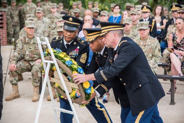 From Left: Regimental Command Sgt. Maj. Christopher Williams; Col. Daryl Hood, U.S. Army CBRN School commandant; and Regimental Warrant Chief Officer 3 Robert Lockwood, place a wreath in remembrance of fallen chemical Soldiers during the Chemical Regimental Week Sunrise Service held June 26 at Chemical Memorial Grove.