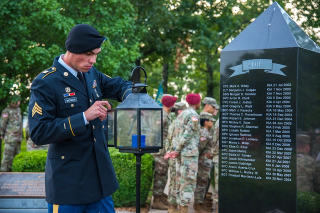 Sgt. Dominik Michalik, CBRN Advanced Leader Course student, lights a candle in remembrance of fallen chemical Soldiers during the Chemical Regiment's Honor to Our Fallen Sunrise Service held June 26 at the Chemical Memorial Grove.