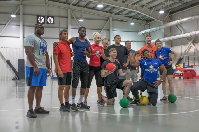 American Gladiators pose with military personnel July 4th, 2019, during a visit to Mihail Kogalniceanu Air Base, Romania. The Gladiator's visit was part of a tour across Europe to entertain and boost the morale of service members and participants through themed competitions and interactive events. (U.S. Army photo by Pvt. Michael Ybarra)